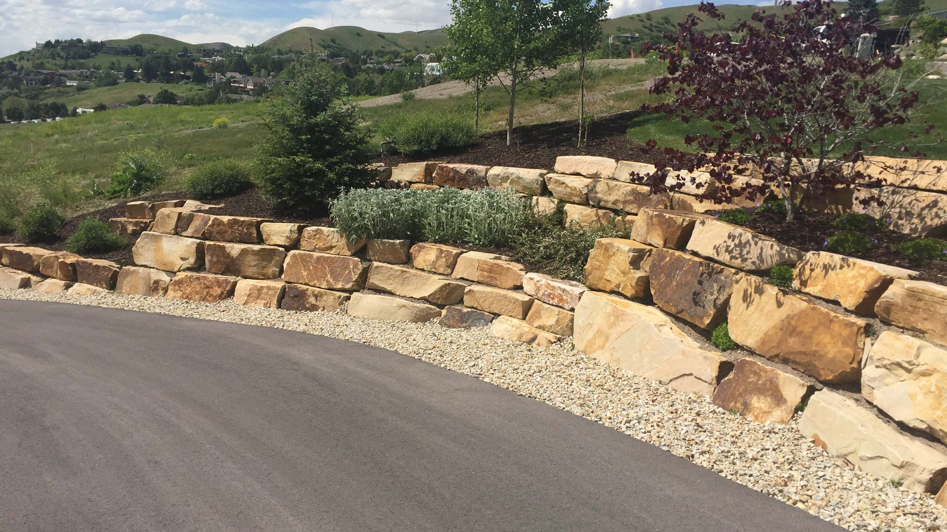 Boulder retaining wall with new mulch and landscaping.