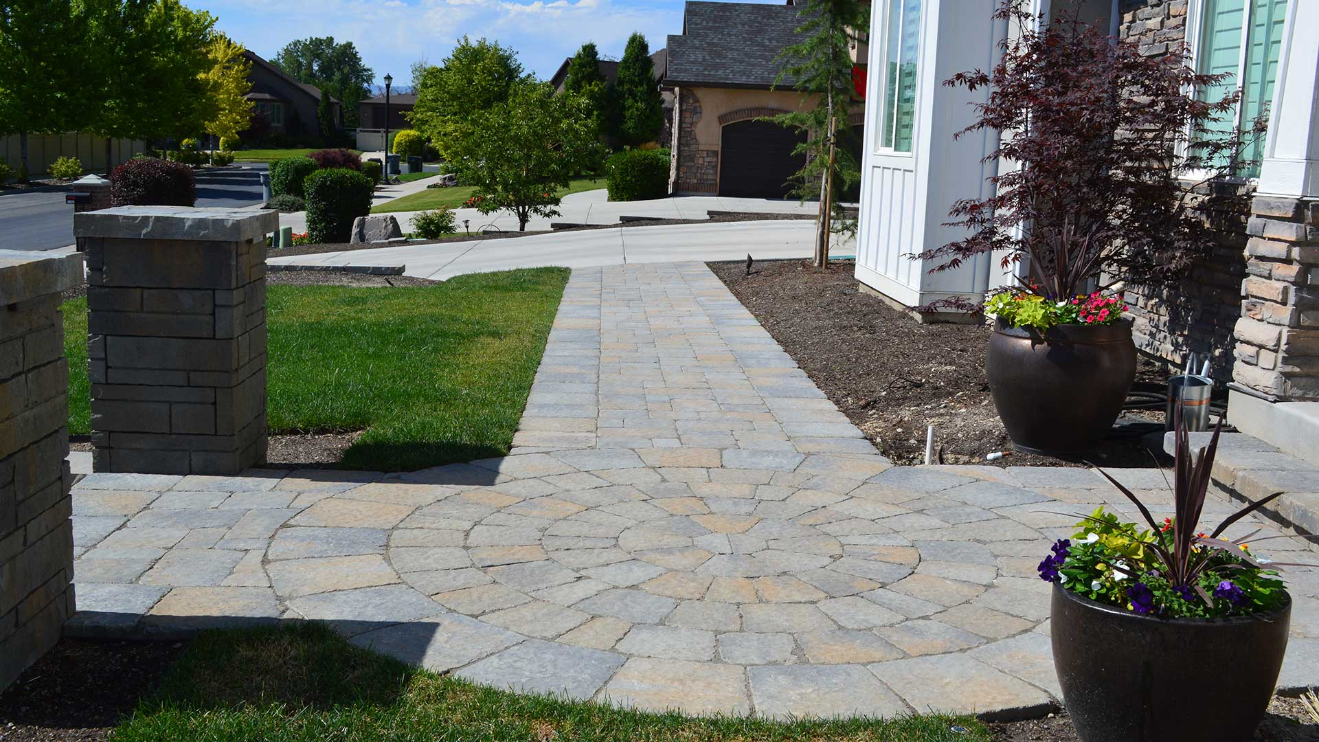 A new patio and walkway recently designed and installed by our professionals at a home in South Jordan.