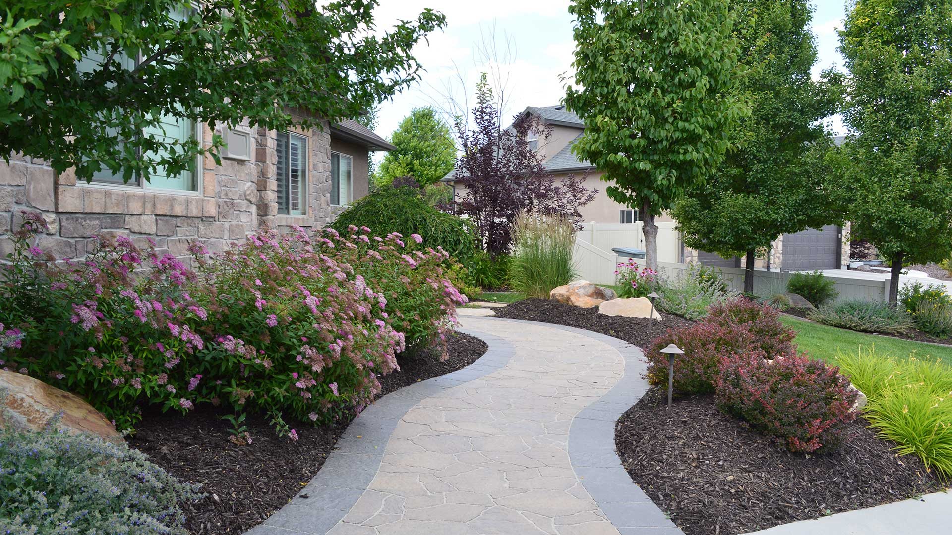 Professionally designed landscaping with mature annuals in front of a home in Salt Lake City, UT.