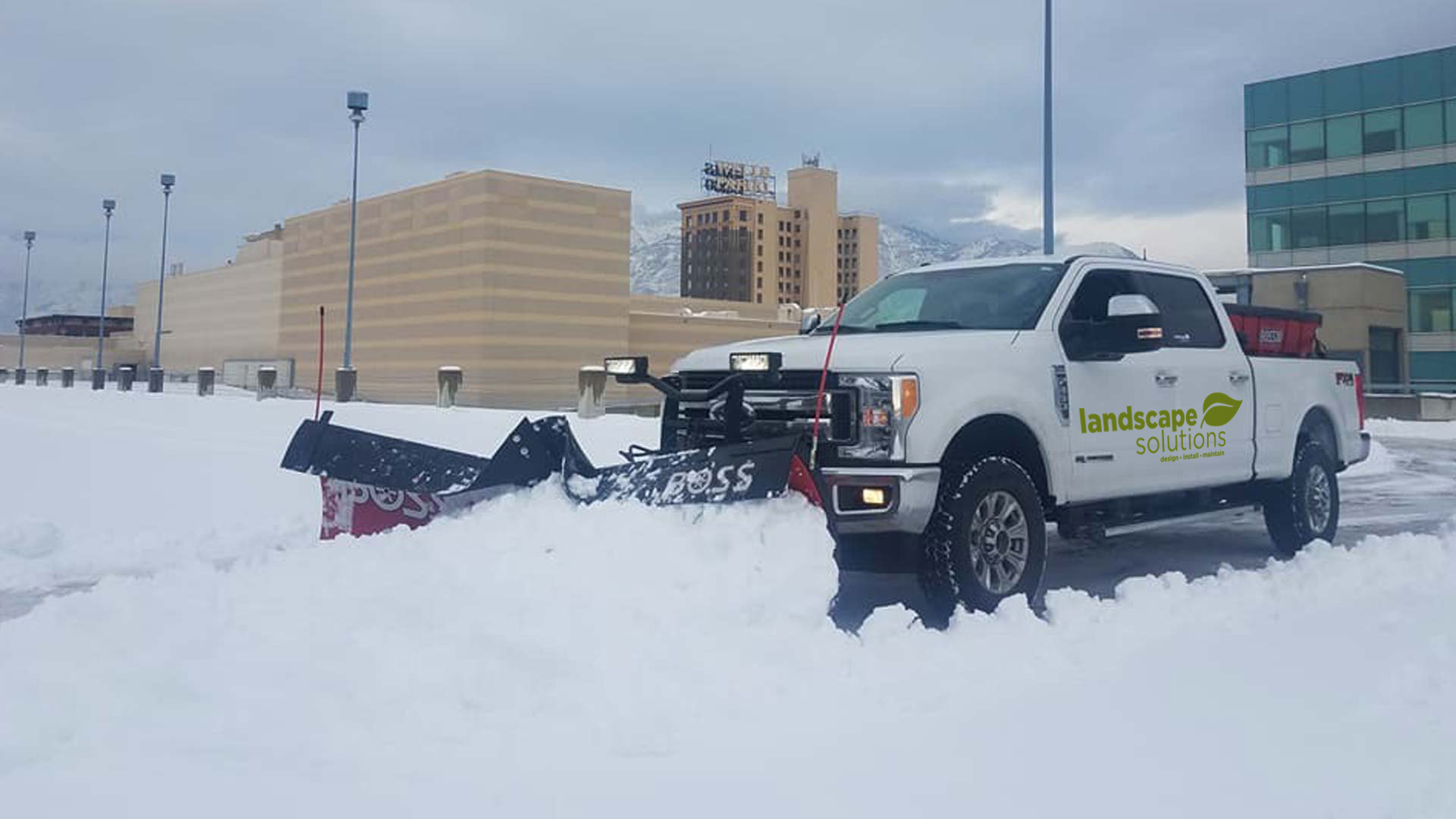 Our truck and plow removing snow from a large commercial parking lot located in Ogden, UT.