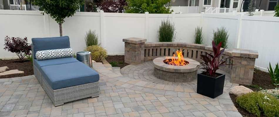 Round fire pit, with a new paver patio, and landscaping in the backyard of a home in Ogden.