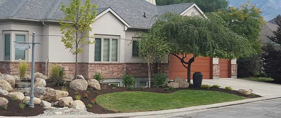 New landscape design including plants, trees, shrubs, flowers, and boulders in front of a home in Draper, UT.